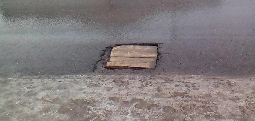 Фотофакт: дорожную яму в Ижевске заделали досками