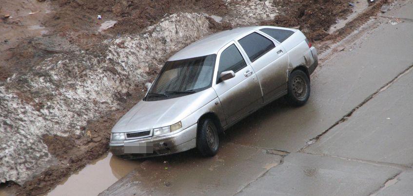 Фотофакт: В Ижевске автомобиль наполовину провалился в траншею