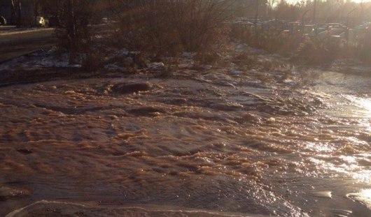 В Ижевске на улице Салютовской потоки ржавой воды текут по дороге